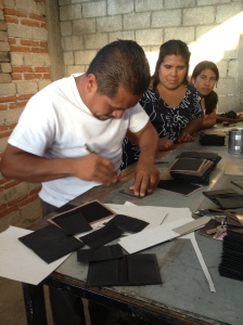 Claudia and her daughter watch as her husband carefully cuts out the leather products she will sell